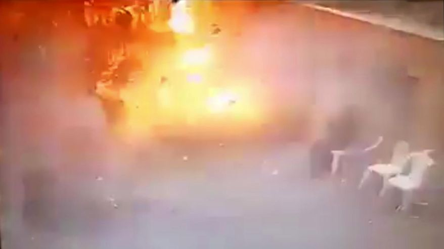 In video made available by Egyptian Interior Ministry, a man sits at right as a suicide bomber detonates at the front gates into St. Mark's Coptic Cathedral in Alexandria, Egypt, Sunday April 9, 2017. The bomber was stopped by security at the gate and forced to go through a metal detector before detonating at the gates.  Bombs exploded at two Coptic churches in different cities in northern Egypt as worshippers were celebrating Palm Sunday, killing dozens of people and wounding many more in an assault claimed by the Islamic State group.(Egyptian Interior Ministry via AP)