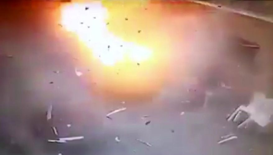 In video made available by Egyptian Interior Ministry, a man sitting at right is engulfed by the blast as a suicide bomber detonates at the front gates into St. Mark's Coptic Cathedral in Alexandria, Egypt, Sunday April 9, 2017. The bomber was stopped by security at the gate and forced to go through a metal detector before detonating outside the gates.  Bombs exploded at two Coptic churches in different cities in northern Egypt as worshippers were celebrating Palm Sunday, killing dozens of people and wounding many more in an assault claimed by the Islamic State group.(Egyptian Interior Ministry via AP)
