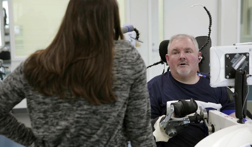 ADVANCE FOR SUNDAY, APRIL 9, 2017 - In this March 2017 photo Jeff Wirth, rights, talks with occupational therapist Erin McNamara at QLI Tri-Dimensional Rehab in Omaha, Neb. Wirth has been at QLI since June after suffering a spinal cord injury in February 2016 that left him a quadriplegic. ( Jeff Damron /The Daily Hub via AP)