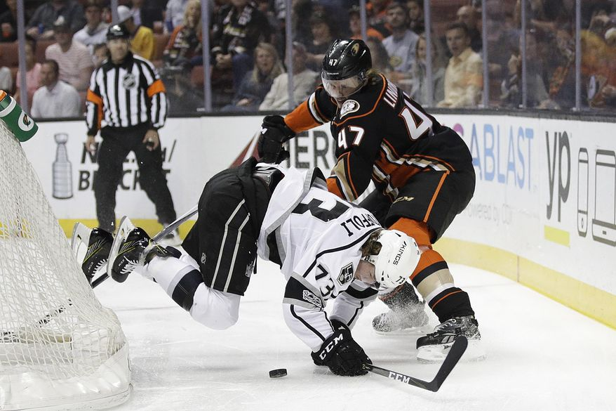 Los Angeles Kings' Tyler Toffoli, bottom, takes a tumble as he fights for the puck with Anaheim Ducks' Hampus Lindholm, of Sweden, during the first period of an NHL hockey game Sunday, April 9, 2017, in Anaheim, Calif. (AP Photo/Jae C. Hong)