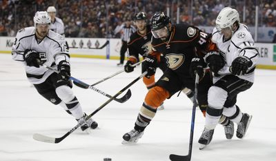 Los Angeles Kings' Anze Kopitar, right, of Slovenia, and Anaheim Ducks' Nate Thompson chase the puck during the first period of an NHL hockey game, Sunday, April 9, 2017, in Anaheim, Calif. (AP Photo/Jae C. Hong)