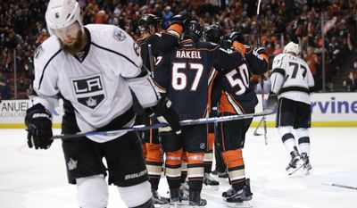 Anaheim Ducks players gather to celebrate a goal by Antoine Vermette as Los Angeles Kings' Jake Muzzin, foreground, skates near by during the second period of an NHL hockey game, Sunday, April 9, 2017, in Anaheim, Calif. (AP Photo/Jae C. Hong)