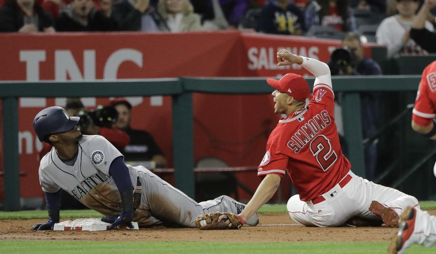 Los Angeles Angels' Andrelton Simmons, right, looks at third base umpire Greg Gibson after applying a tag on Seattle Mariners' Jean Segura during the third inning of a baseball game Saturday, April 8, 2017, in Anaheim, Calif. Segura was called out after a video review. (AP Photo/Jae C. Hong)