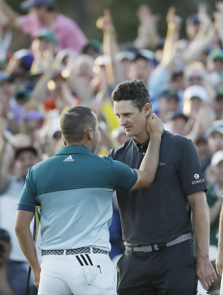Sergio Garcia, of Spain, is hugged by Justin Rose, of England, after making his birdie putt on the 18th green to win the Masters golf tournament after a playoff Sunday, April 9, 2017, in Augusta, Ga. (AP Photo/David Goldman)