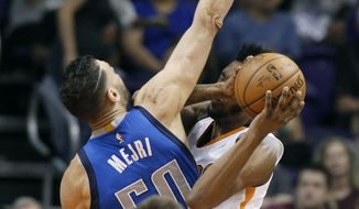 Dallas Mavericks center Salah Mejri (50) defends the shot of Phoenix Suns forward Derrick Jones Jr., right, during the first half of an NBA basketball game, Sunday, April 9, 2017, in Phoenix. (AP Photo/Ralph Freso)