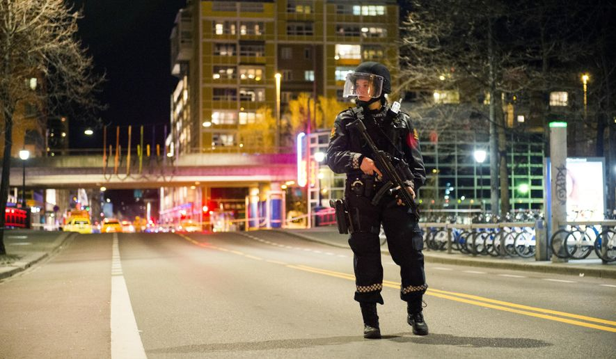 """An officer stands guard as police cordon off a large area around a subway station on a busy commercial street Saturday night, April 8, 2017, after finding what they described as a """"bomb-like"""" device, in Oslo, Norway. The official police Twitter account said one man has been arrested and Police Chief Vidar Pedersen said police were working to disarm it. (Fredrik Varfjell /NTB scanpix via AP)"""