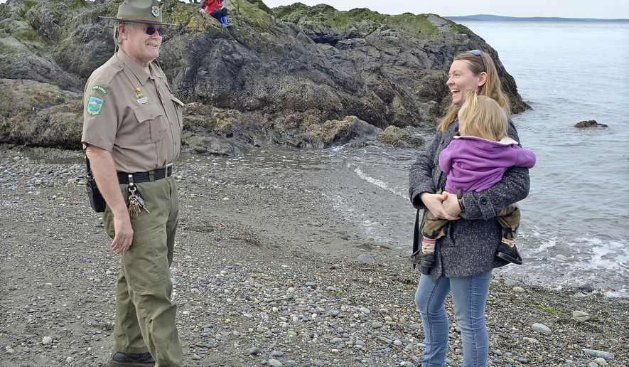 In this March 20, 2017, photo, retiring assistant park manager at Deception Pass State Park Rick Blank talks to visitor Brianna Lyon, holding her youngest child, Kestrel at West Beach in Washington. Blank has been an employee of Washington State Parks for 45 years and is the longest-tenured ranger in the field, he arrived at Deception Pass in 1990. (Scott Terrell/Skagit Valley Herald via AP)