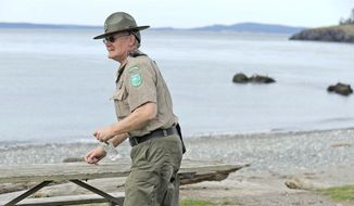 In this March 20, 2017, file photo, retiring assistant park manager Rick Blank grabs a water bottle left on a park bench at West Beach at Deception Pass State Park in Washington. Blank has been an employee of Washington State Parks for 45 years and is the longest-tenured ranger in the field, he arrived at Deception Pass in 1990. (Scott Terrell/Skagit Valley Herald via AP) ** FILE **