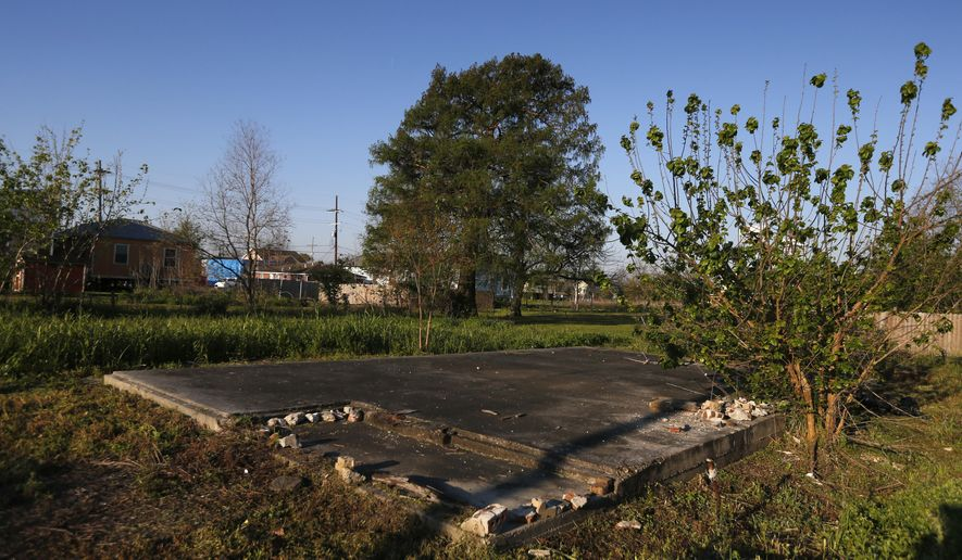 In this Thursday, March 16, 2017 photo, a slab of a former home sits in an empty lot in the Lower 9th Ward in New Orleans. A major rebuilding project is set to bring hundreds of new residents into the neighborhood, in what developers, officials and some residents hope will mark an important turning point. But others have concerns about the new development and whether it's the right fit for the historic, African-American neighborhood. (AP Photo/Gerald Herbert)