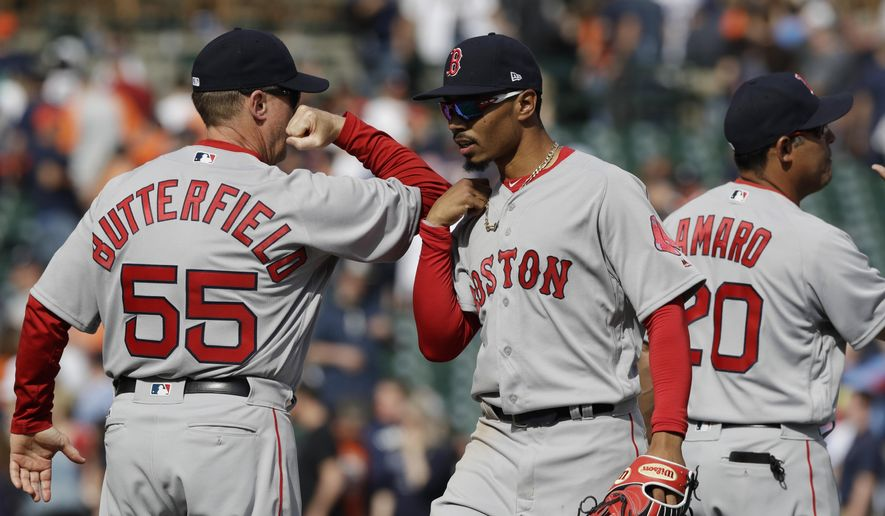 Boston Red Sox third base coach Brian Butterfield greets outfielder Mookie Betts after the team's 7-5 win over the Detroit Tigers in a baseball game, Sunday, April 9, 2017, in Detroit. (AP Photo/Carlos Osorio)