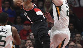 Portland Trail Blazers guard Damian Lillard drives to the basket as Utah Jazz forward Gordon Hayward, right, defends during the first half of an NBA basketball game in Portland, Ore., Saturday, April 8, 2017. (AP Photo/Steve Dykes)