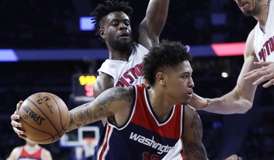 Washington Wizards forward Kelly Oubre Jr. (12) drives on Detroit Pistons forward Reggie Bullock and center Boban Marjanovic, right, during second half of an NBA basketball game, Monday, April 10, 2017, in Auburn Hills, Mich. (AP Photo/Carlos Osorio)