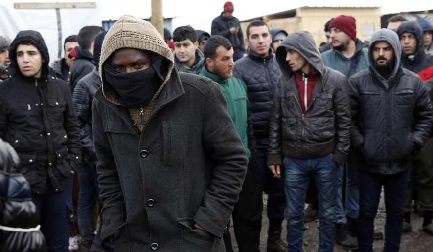 Migrants watch French officials tour  a makeshift camp set outside Calais, France, Tuesday Feb. 23, 2016. People fleeing conflict and poverty in Africa, the Mideast and Asia are facing an evening deadline to move out of the camp in the French port of Calais that has become a flashpoint in Europe's migrant crisis. (AP Photo/Jerome Delay)