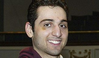 FILE - In this Feb. 17, 2010, file photo, Tamerlan Tsarnaev smiles after accepting the trophy for winning the 2010 New England Golden Gloves Championship in Lowell, Mass. The FBI says one of the Boston Marathon bombers told agents in 2011 that four young men in suits had gone looking for him but never returned and he didn't know why. The revelation came in an FBI interview report released Monday, April 10, 2017. The FBI previously acknowledged interviewing bomber Tamerlan Tsarnaev two years before the marathon attack. Tsarnaev died during a police confrontation days after the April 15, 2013, attack, which killed three people and injured hundreds. (Julia Malakie/The Lowell Sun via AP, File)