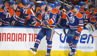 Edmonton Oilers' Connor McDavid (97) and Leon Draisaitl (29) celebrate a goal against the Vancouver Canucks during the third period of an NHL hockey game in Edmonton, Alberta, Sunday, April 9, 2017. (Amber Bracken/The Canadian Press via AP)