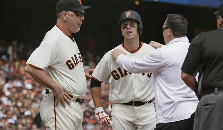 San Francisco Giants' Buster Posey, center, is checked by a trainer as manager Bruce Bochy, left, looks on after Posey was hit in the helmet by a fastball thrown by Arizona Diamondbacks starting pitcher Taijuan Walker in the first inning of a baseball game Monday, April 10, 2017, in San Francisco. Posey was forced out of the game. (AP Photo/Eric Risberg)