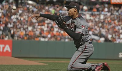 Arizona Diamondbacks starting pitcher Taijuan Walker throws the ball to catcher Jeff Mathis at home plate after the San Francisco Giants' Matt Moore grounded into a fielder's choice in the fourth inning of a baseball game Monday, April 10, 2017, in San Francisco. The Giants' Brandon Crawford scored from third base on the play and Walker was given a throwing error. The Giants scored two other runs following the play and Mathis was given a throwing error. (AP Photo/Eric Risberg)