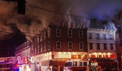 Firefighters respond to a structure blaze in Portsmouth, N.H., early Monday, April 10, 2017. WFXT-TV in Boston reported that the building houses the State Street Saloon. (Ioanna Raptis/Portsmouth Herald via AP)