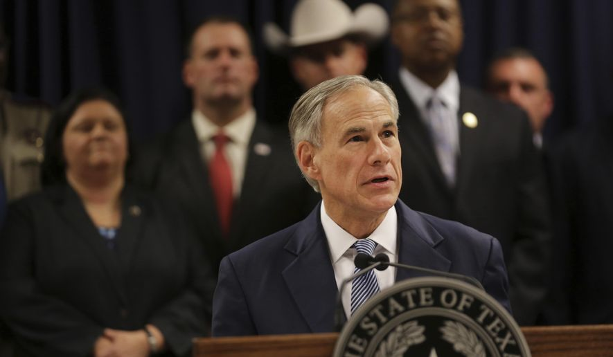 Surrounded by leadership of different law enforcement agencies, Texas Gov. Greg Abbott speaks during a new conference Monday, April 10, 2017, in Houston. Abbott on Monday announced that he would direct state grant money and additional Texas Rangers law enforcement resources to monitor and solve gang crimes in Harris County. (Marie D. De Jesus /Houston Chronicle via AP)