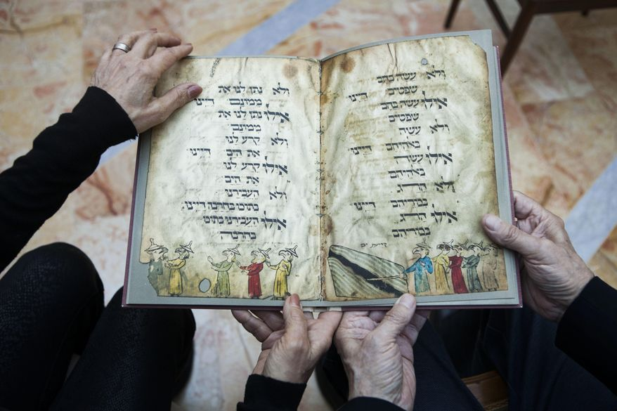 File - In this file photo taken Wednesday, April 13, 2016, Eli and Shuli Barzilai hold a copy of the Birds' Head Haggadah, the text read around Jewish dinner tables on the Passover holiday, in their home in Jerusalem. Last year, the descendants of German Jewish lawmaker Ludwig Marum requested the Israel Museum pay compensation for the famed Bird's Head Haggadah. They say the Haggadah was snatched from their grandfather's family after he was rounded up by the Nazis and later sold to the predecessor of the Israel Museum in Jerusalem without their consent. (AP Photo/Dan Balilty, File)