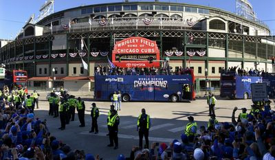 FILE - In this Nov. 4, 2016, file photo, a parade honoring the World Series champion Chicago Cubs passes Wrigley Field in Chicago. In a home opener unlike any other at Wrigley Field, the Cubs will raise a banner as defending World Series champions for the first time since they moved into the venerable ballpark more than a century ago. (AP Photo/Paul Beaty, File)