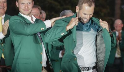 Danny Willett of England, puts a green jacket on Sergio Garcia, of Spain, after the Masters golf tournament, Sunday, April 9, 2017, in Augusta, Ga. (AP Photo/Chris Carlson)