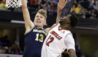 FILE - In this Sunday, March 19, 2017, file photo, Michigan forward Moe Wagner (13) shoots over Louisville forward Mangok Mathiang (12) during the second half of a second-round game in the men's NCAA college basketball tournament in Indianapolis. Michigan standouts Wagner and D.J. Wilson are entering their names into the NBA draft without hiring agents. (AP Photo/Michael Conroy, File)