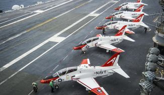 """In this Dec. 10, 2016 photo, pilots perform pre-flight procedures in T-45C Goshawks from Training Air Wing One on the flight deck of the aircraft carrier USS George Washington docked in Norfolk, Va. The U.S. Navy continues to ground a fleet of training jets because of a spike in problems with their oxygen breathing systems. Vice Admiral Mike Shoemaker wrote in a Navy blog post Sunday, April 9, 2017, that instructor pilots have raised concerns over potential """"physiological episodes"""" in the cockpit. (Petty Officer 2nd Class Bryan Mai/U.S. Navy via AP)"""