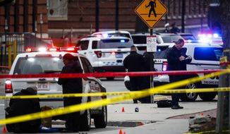 FILE - In this Nov. 28, 2016, file photo, crime scene investigators collect evidence from the pavement as police respond to an attack on the Ohio State University campus in Columbus, Ohio. Ohio State University is beefing up its emergency alert system and streamlining the way officials communicate in a crisis after a November car-and-knife attack exposed some flaws in the text-message procedure. (AP Photo/John Minchillo, File)