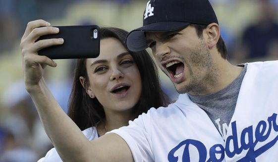 FILE- In this Oct. 19, 2016, file photo, Ashton Kutcher and wife Mila Kunis take a selfie before Game 4 of the National League baseball championship series between the Chicago Cubs and the Los Angeles Dodgers in Los Angeles. Kutcher offered emotional praise for his wife Mila Kunis, his twin brother and the rest of his family in accepting an award for character in his native Iowa on April 9, 2017. (AP Photo/David J. Phillip, File)