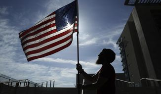 A protester holds up a flag outside of a federal courthouse, Monday, April 10, 2017, in Las Vegas. The protester and others stood outside the courthouse in support of six defendants accused of wielding weapons against federal agents during a 2014 standoff involving cattleman and states' rights advocate Cliven Bundy. (AP Photo/John Locher)