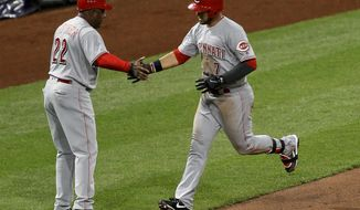 Cincinnati Reds' Eugenio Suarez (7) is greeted by third base coach Billy Hatcher (22) as he rounds the bases after hitting a solo home run off Pittsburgh Pirates relief pitcher Wade LeBlanc in the fifth inning of a baseball game, Monday, April 10, 2017, in Pittsburgh. (AP Photo/Keith Srakocic)