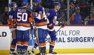 New York Islanders center Brock Nelson (29) celebrates with teammates after scoring a goal against the Ottawa Senators in the second period of an NHL hockey game, Sunday, April 9, 2017, in New York. (AP Photo/Adam Hunger)