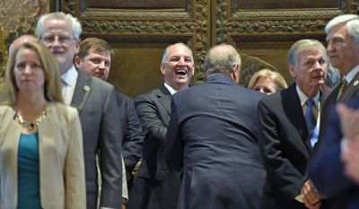 Accompanied by his wife Donna Edwards, right partially obscured, Gov. John Bel Edwards, center, laughs while waiting to enter the House chamber to address the joint session during opening day at the Louisiana legislature Monday April 10, 2017, in Baton Rouge, La.  (Bill Fig/The Advocate via AP, Pool)