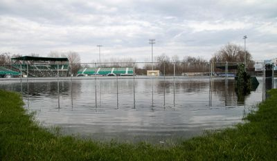In this Sunday, April 9, 2017 photo, water fills Homer Stryker Field in Kalamazoo, Mich. Flooding in southwestern Michigan has closed several roadways and swamped the home of the Kalamazoo Growlers baseball team while severe thunderstorms caused damage in the Upper Peninsula. (Jake Green/Kalamazoo Gazette-MLive Media Group via AP)