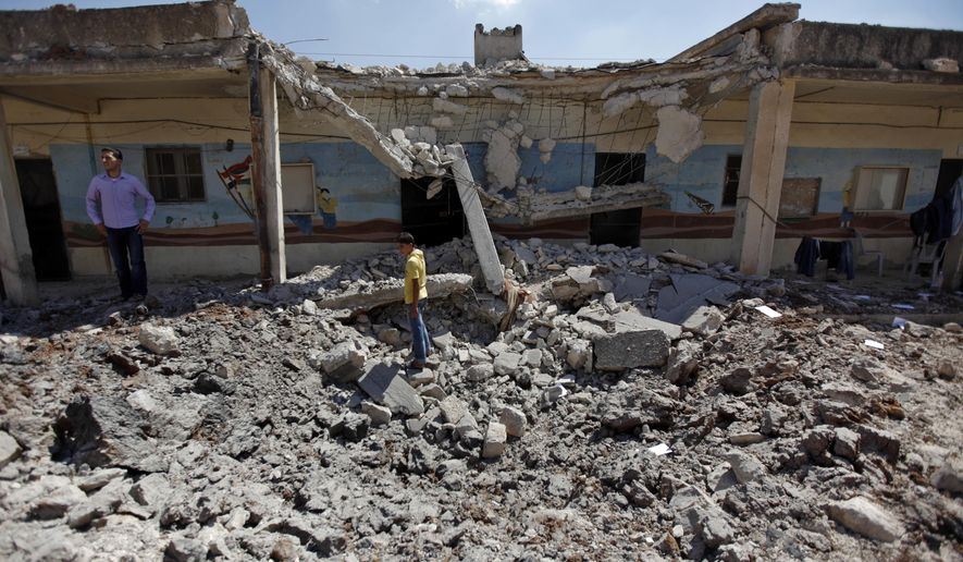 FILE - In this Wednesday, Aug. 8, 2012 file photo, Syrians check the damage of a destroyed school after it was hit by an air strike killing six Syrians in town of Tal Rifat on the outskirts of Aleppo city, Syria. With its missile strike on Shayrat Airbase in central Syria, Washington signaled that it had judged President Bashar Assad responsible for the horrific chemical weapons attack in north Syria that drew international outrage last week. But it is not the first or even deadliest atrocity of the war. (AP Photo/ Khalil Hamra, FILE)