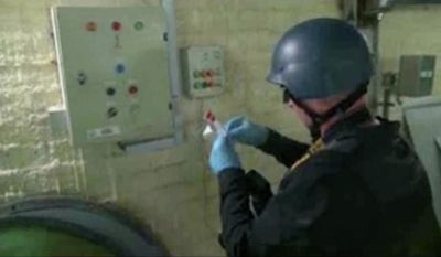 FILE - This file image made from video broadcast on Syrian State Television on Tuesday, Oct. 8, 2013, purports to show a chemical weapons expert taking samples at a chemical weapons plant at an unknown location in Syria. With its missile strike on Shayrat Airbase in central Syria, Washington signaled that it had judged President Bashar Assad responsible for the horrific chemical weapons attack in north Syria that drew international outrage last week. But it is not the first or even deadliest atrocity of the war. (AP Photo/Syrian State Television via AP video, File)
