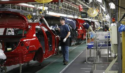 FILE - In this Thursday, Feb. 18, 2010, file photo, Toyota employee Vince Tharpe installs headliners in new Camrys at the Toyota Motor Manufacturing, Kentucky plant in Georgetown, Ky. Toyota said Monday, April 10, 2017, it is investing $1.3 billion to retool its sprawling Georgetown factory, where the company's flagship Camry sedans are built. No new factory jobs are being added, but Toyota says the upgrades amount to the biggest single investment ever at one of its existing plants in the United States. (AP Photo/Ed Reinke, File)