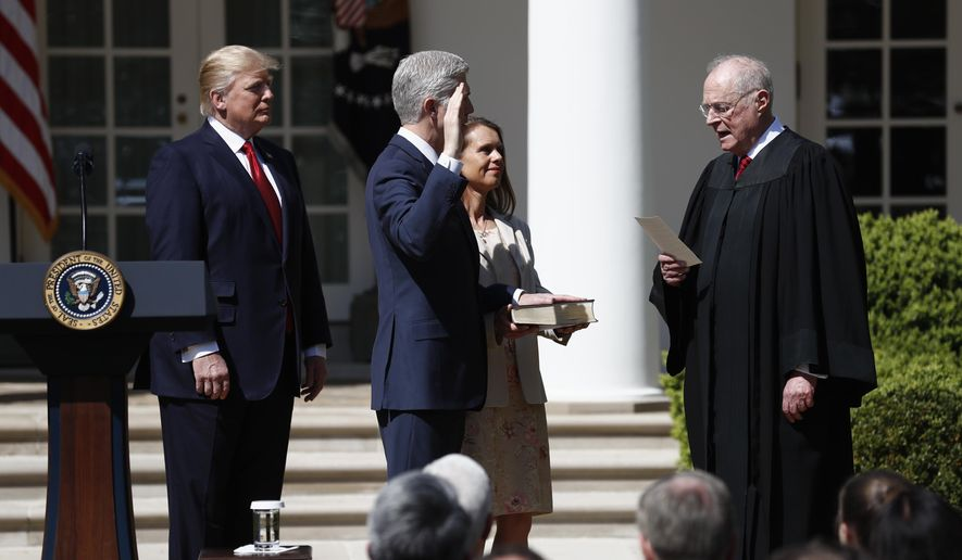 President Donald Trump watches as Supreme Court Justice Anthony Kennedy administers the judicial oath to Justice Neil Gorsuch during a re-enactment in the Rose Garden of the White House White House in Washington, Monday, April 10, 2017. Holding the bible is Gorsuch's wife Marie Louise Gorsuch. (AP Photo/Carolyn Kaster)