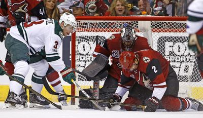 Arizona Coyotes' Luke Schenn (2) helps goalie Mike Smith, back right, stop the puck on a shot from Minnesota Wild's Charlie Coyle (3) during the second period of an NHL hockey game Saturday, April 8, 2017, in Glendale, Ariz. (AP Photo/Ross D. Franklin)