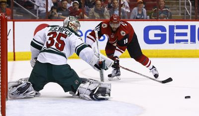 Arizona Coyotes' Anthony Duclair (10) passes the puck past Minnesota Wild's Darcy Kuemper (35) during the second period of an NHL hockey game Saturday, April 8, 2017, in Glendale, Ariz. (AP Photo/Ross D. Franklin)