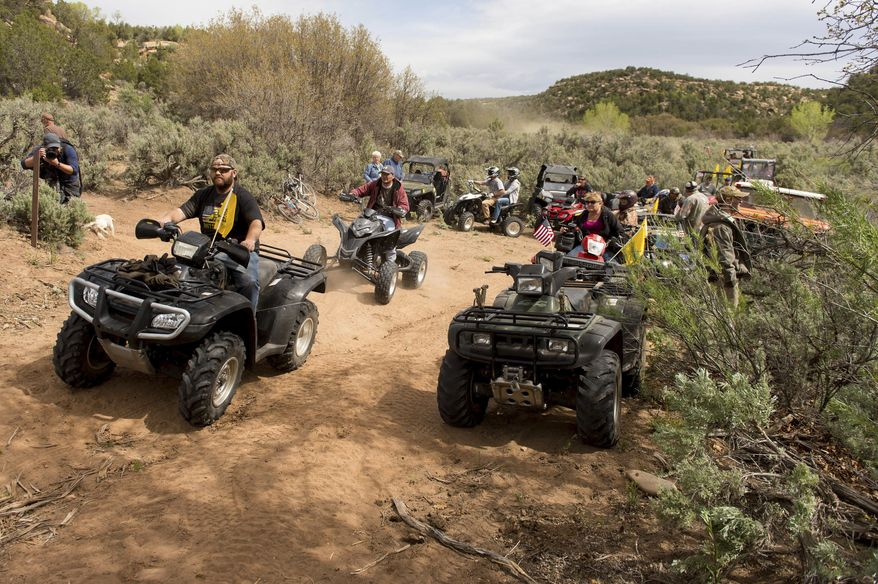 FILE - In this May 10, 2014, file photo, Ryan Bundy, son of the Nevada rancher Cliven Bundy, rides an ATV into Recapture Canyon north of Blanding, Utah, in a protest against what demonstrators call the federal government's overreaching control of public lands. U.S. Interior Secretary Ryan Zinke has lifted a ban on motorized vehicles in some parts of a southeastern Utah canyon that was the setting of a 2014 ATV protest ride that was a flashpoint in the Western struggle over government land management. Zinke said in a news release Monday, April 10, 2017, in that providing recreation access on public lands is important and that disabled people can't get around without motorized vehicles. (The Salt Lake Tribune, Trent Nelson via AP, File)