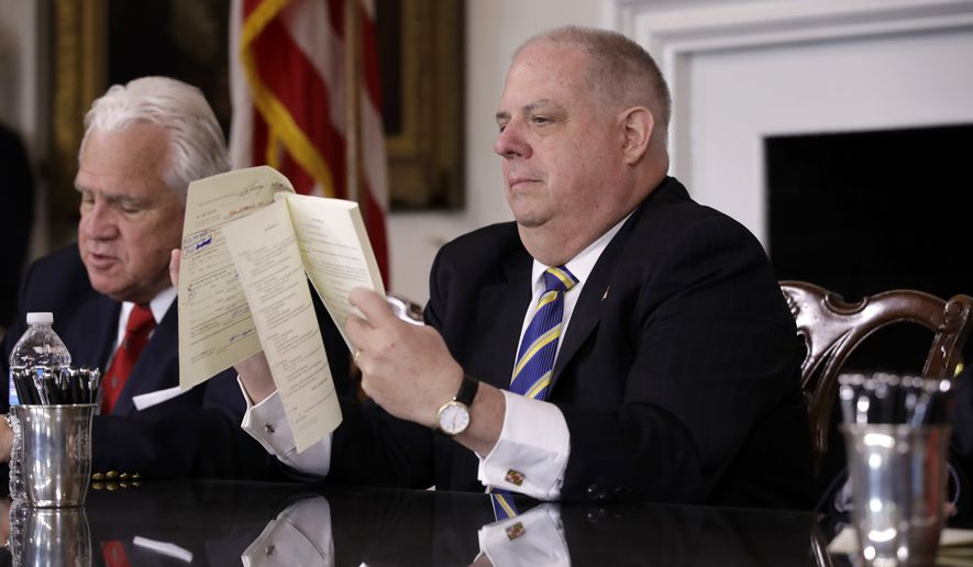 Maryland Gov. Larry Hogan flips through a bill before signing it Tuesday at the State House in Annapolis. (Associated Press)