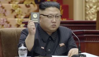 In this image made from video released by North Korean broadcaster KRT on Tuesday, April 11, 2017, North Korean leader Kim Jong Un holds up the Supreme People's Assembly card in Pyongyang, North Korea. North Korea's parliament convened Kim Jong Un taking the center seat. The Supreme People's Assembly normally meets once or twice a year at the Mansudae Assembly Hall in central Pyongyang. (KRT via AP)