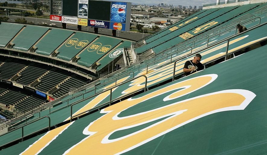 File - In this March 15, 2006 file photo, Mike Lawson, center right, affixes a green tarp over upper deck seats at McAfee Coliseum in Oakland, Calif. The Oakland Athletics are pulling the tarps and opening the upper deck at the Coliseum for their upcoming 10-game homestand. The seats will sell for $15 and be available for games beginning Friday against Houston, the team said Tuesday, April 11, 2017. (AP Photo/Ben Margot, File)