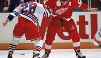 FILE - In this Dec. 2, 1992, file photo, New York Rangers Tie Domi (28) fights with Detroit Red Wings Bob Probert (24) less than a minute into the first period of the game at New York's Madison Square Garden. Probert's widow, Dani, sprinkled some of the late enforcer's ashes in the penalty box during the final game at Detroit's Joe Louis Arena on April 9, 2017.  (AP Photo/Ron Frehm, File)