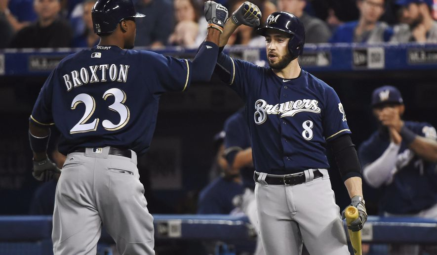 Milwaukee Brewers' Keon Broxton (23) celebrates his solo home run against the Toronto Blue Jays with teammate Ryan Braun (8) during the first inning of a baseball game in Toronto on Tuesday, April 11, 2017. (Nathan Dennette/The Canadian Press via AP)