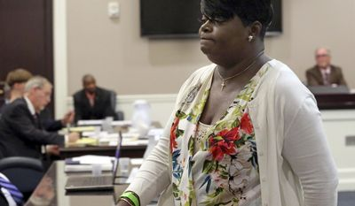 """Nadine Lance Collier, Ethel Lance's daughter walks past Dylann Roof, seated at the defense table in the Charleston County Court Monday April 10, 2017 after she addressed the court during his guilty plea hearing on murder charges in Charleston,S.C. """" I'm the one who forgave you in the bond hearing, and I still do"""" said Collier. The convicted Charleston church shooter, Roof was given nine consecutive life sentences in state prison after he pleaded guilty to state murder charges Monday, leaving him to await execution in a federal prison and sparing his victims and their families the burden of a second trial. (Grace Beahm/The Post And Courier via AP, Pool)"""
