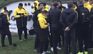 Head coach Thomas Tuchel, center, is surrouned by players after the bus of Borussia Dortmund was damaged after an explosion before the Champions League quarterfinal soccer match against AS Monaco in Dortmund, western Germany, Tuesday, April 11, 2017. (Carsten Linhoff/dpa via AP)