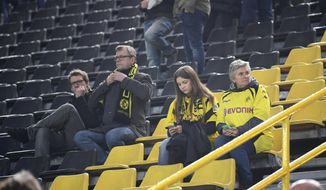 Borussia Dortmund fans sit in the Signal Iduna Park in Dortmund, Germany, Tuesday, April 11, 2017. The first leg of the Champions League quarter final soccer match between Borussia Dortmund and AS Monaco had been  cancelled. (AP Photo/Federico Gambarini/dpa via AP)